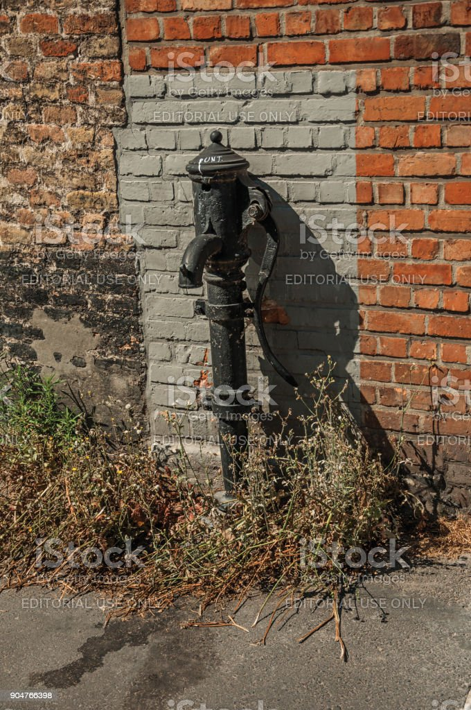 Old street water pump made in iron in front of a brick wall at the city of Bruges. stock photo