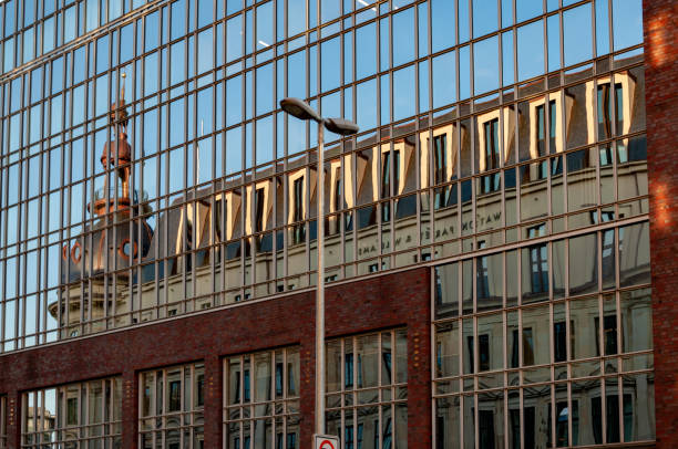 Old streetlight in front of glass wall with distorted reflection of historic chapel and windows on rooftop stock photo