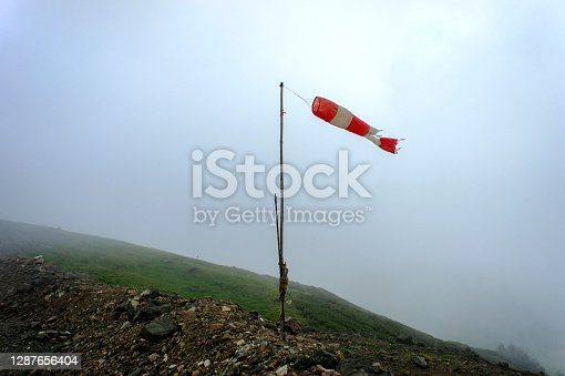 Old striped red-white windsock, indicator of the strength and direction of the wind in the Caucasus mountains in the fog, Aibga ridge, hike, trekking, travel