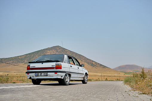 24.07.2021. Nevsehir. Turkey. Old style car Renault white flash on village and gravel road with small hill background.