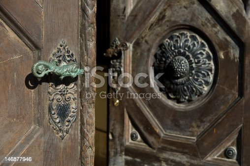 old style entrance door, made of carved massive wood and metal ornamented handle
