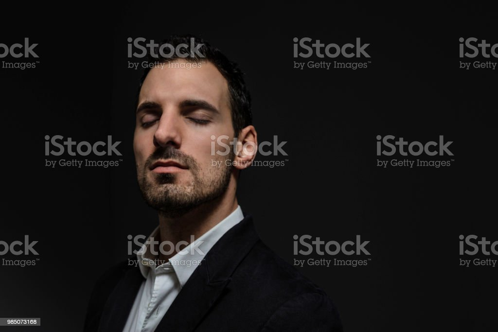 old style man, in elegant suit, isolated on dark background, portrait of an elegant businessman with closed eyes focuses on the challenges to be faced stock photo