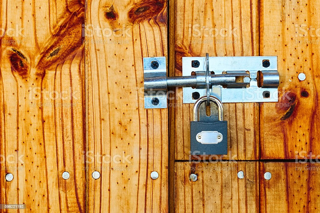 Old style metal lock and padlock on wooden door foto royalty-free