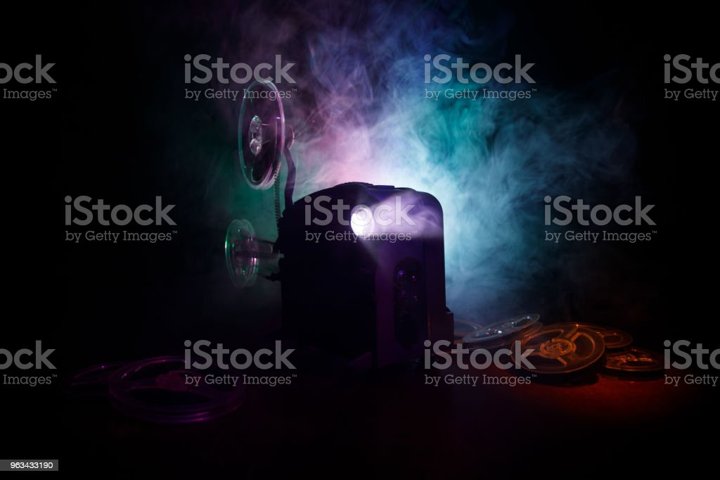 Old style movie projector, close-up. Film projector on a wooden background with dramatic lighting and selective focus. Movies and entertainment concept - Zbiór zdjęć royalty-free (Antyczny)