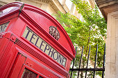 old style red telephone box in a leafy London square, England
