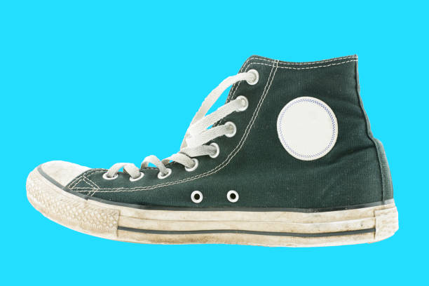 Old style weathered black basketball shoe isolated on baby blue background Old style weathered black basketball shoe isolated on baby blue background all star stock pictures, royalty-free photos & images