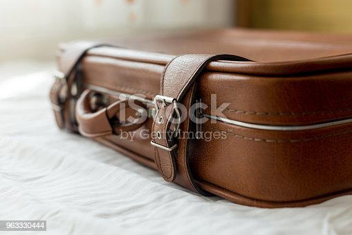 istock Old suitcase on bed 963330444