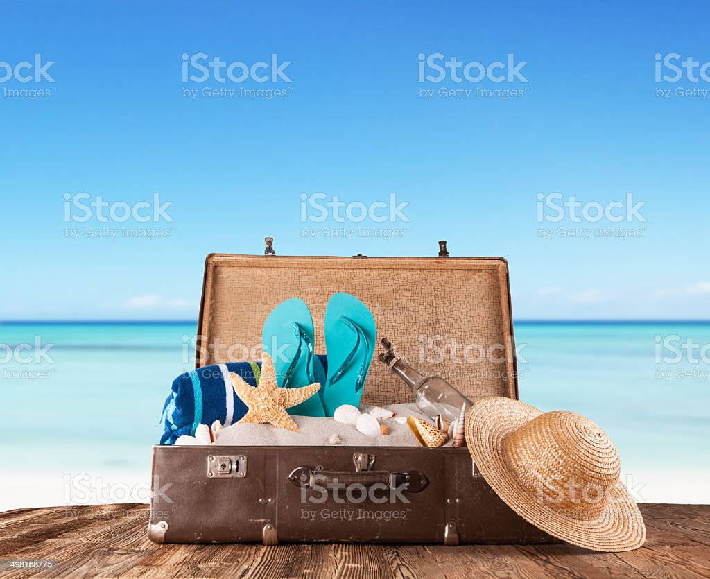 Old suitcase with accessories on beach stock photo