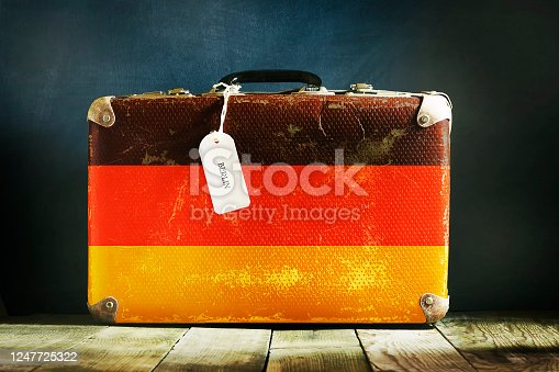 Old suitcase with Germany flag on wooden background. Travels.
