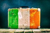 Old suitcase with the Ireland flag on wooden background. Travels