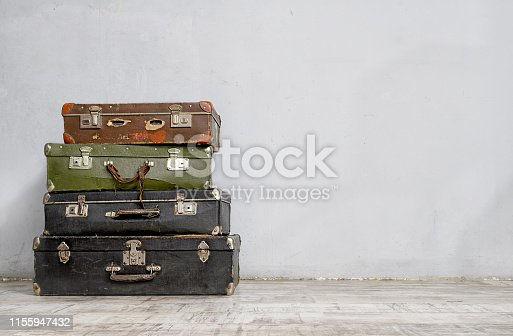 Old suitcases stack near the white concrete wall in an empty room. Retro style luggage concept with copy space.
