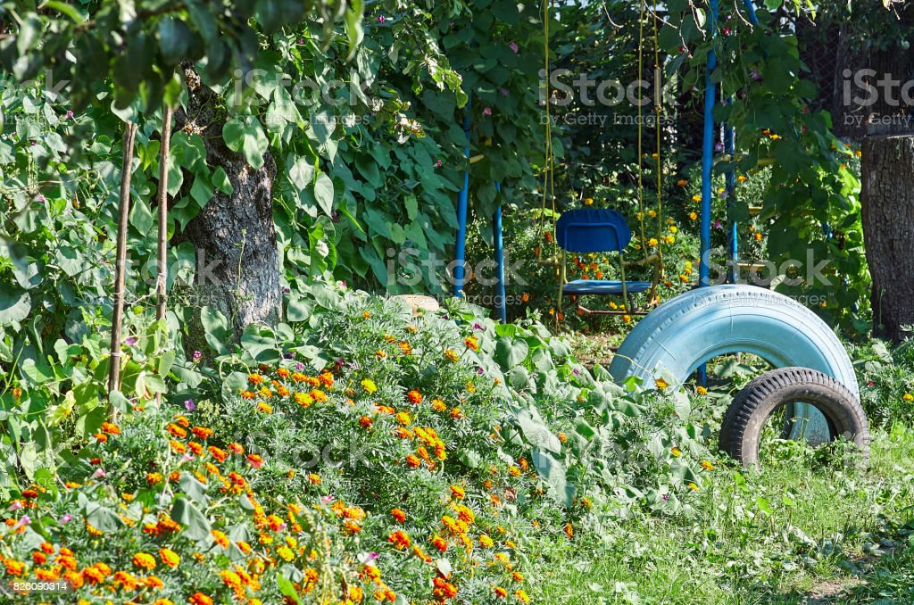 Old swing between flowers in a garden with painted tires stock photo