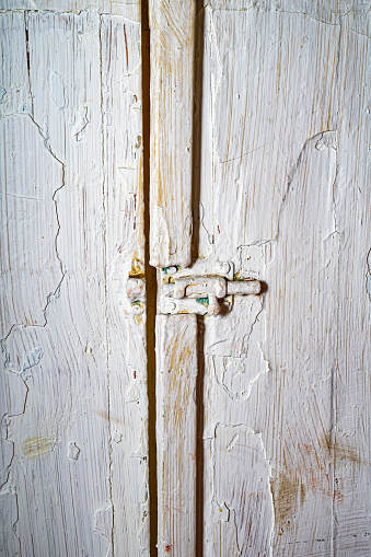 old swing doors covered in cracked white paint. Old doors with a latch in the closet