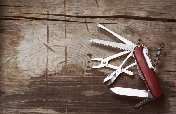 old Swiss knife on a wooden background stock photo