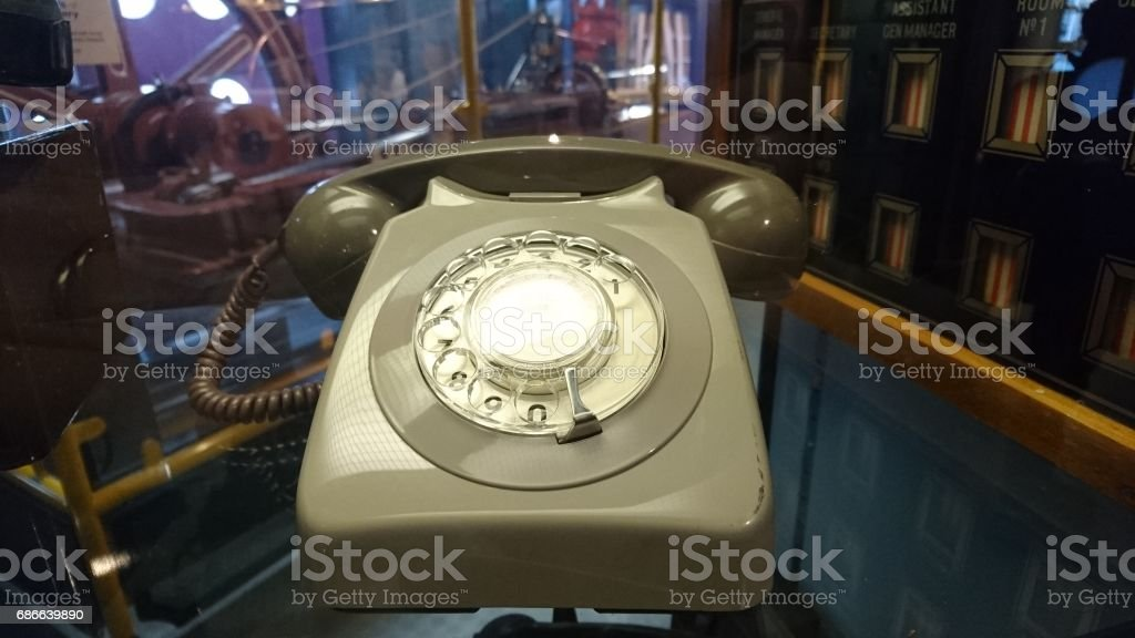 Old sytle dial telephone on a glass desk royalty-free stock photo