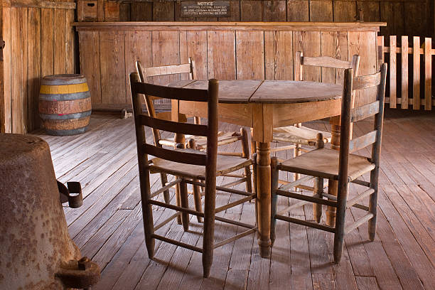 Old Table, Chairs, and Bar at Judge Roy Beans Saloon. Rustic table, chairs, wood floor, and bar, lit by natural light through open door at Judge Roy Beans'