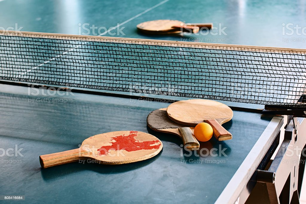 Old table tennis rackets on the game table stock photo