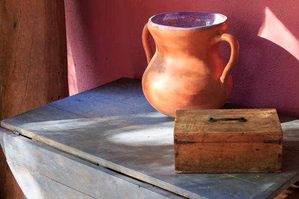 Old table with pottery urn and wooden box. stock photo