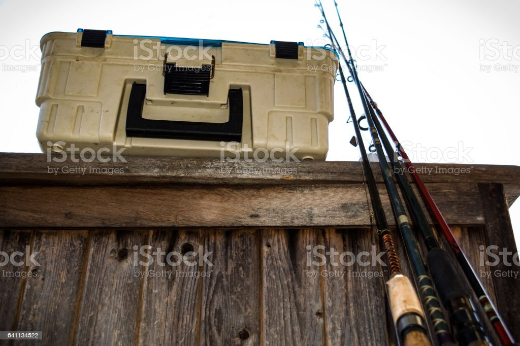 Old tackle box with miscellaneous fishing rods on a fishing trip. stock photo