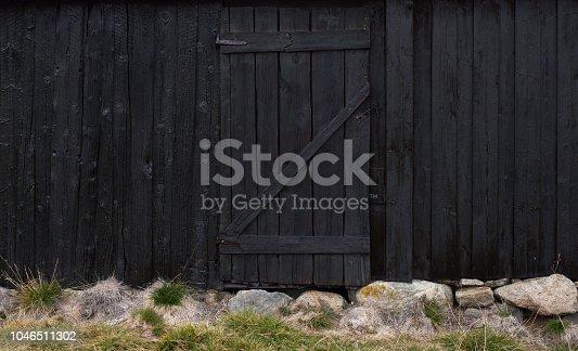 Very dark shed exterior wall with door.