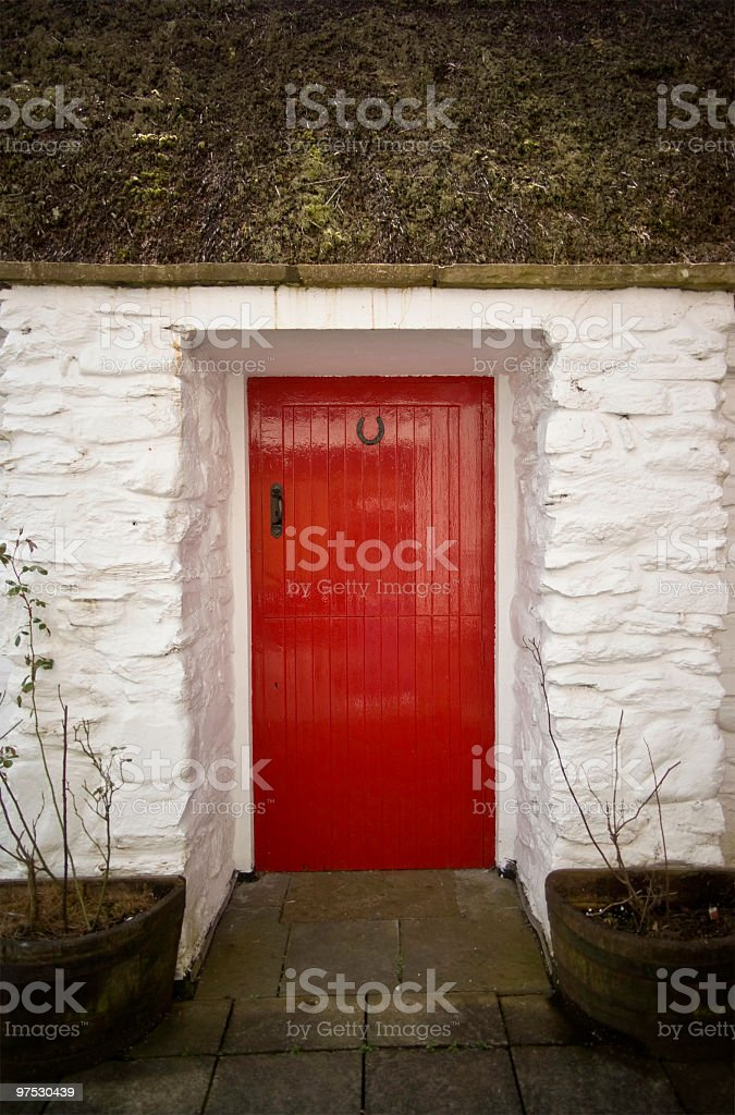 Old tatched Irish country cottage with  Red door royalty-free stock photo