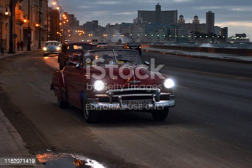 Havana, Cuba - January 20, 2016: Old taxi car driving on the street in Havana during the dusk. The old-styled American vehicles from 50s are the one of the most popular cars in Cuba.