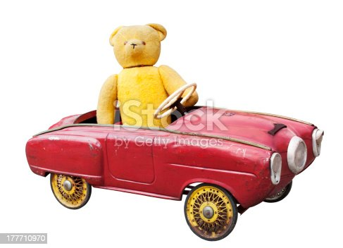 Old teddy bear in a vintage toy car isolated on white