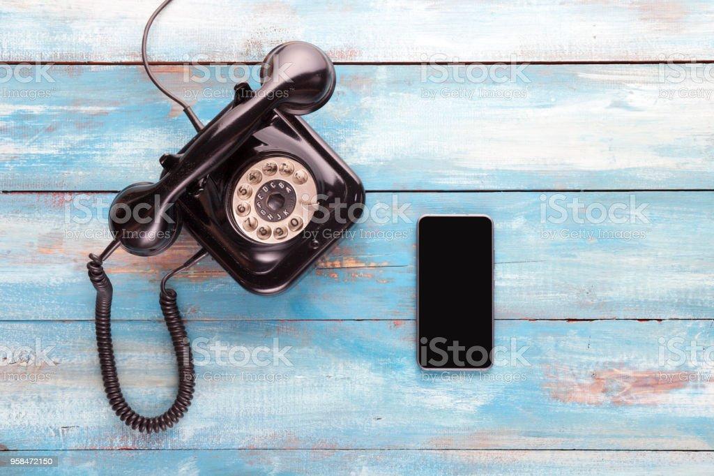 Alte Telefon und Handy auf einem blauen Holzbrett – Foto