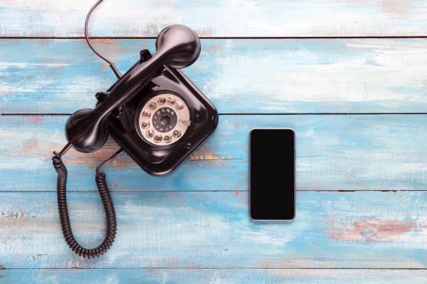 vieux téléphone et téléphone portable sur une planche en bois bleue - neuf photos et images de collection