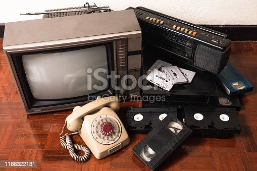 Old telephone and obsolet electronic equipment on wooden floor