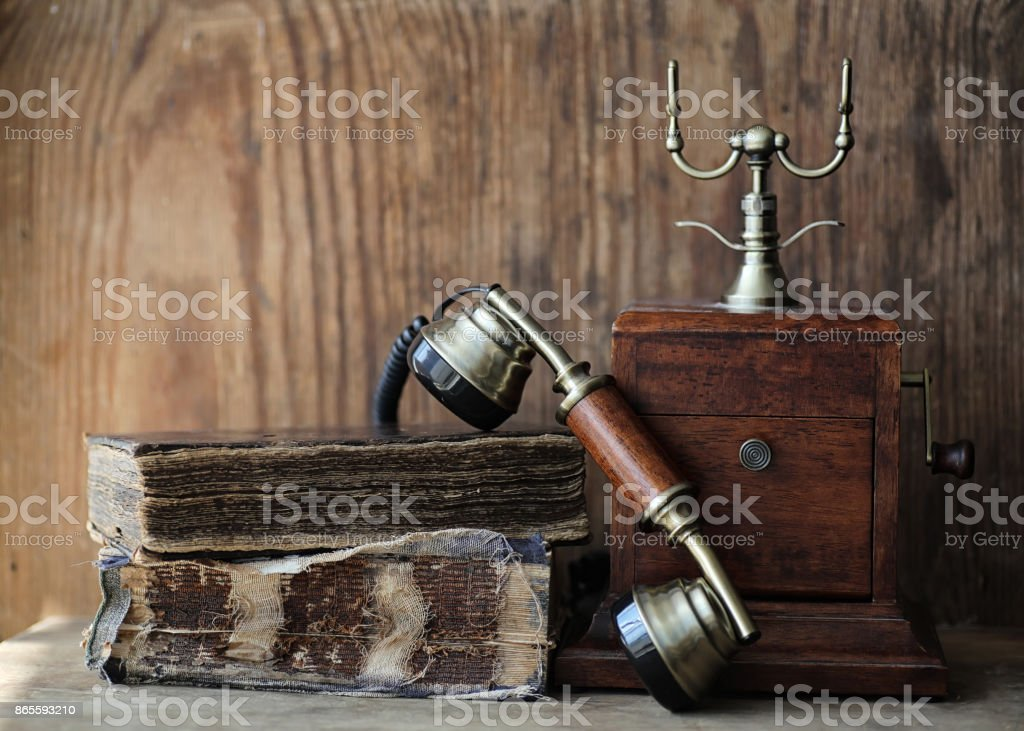 Old telephone and retro book on a wood stock photo