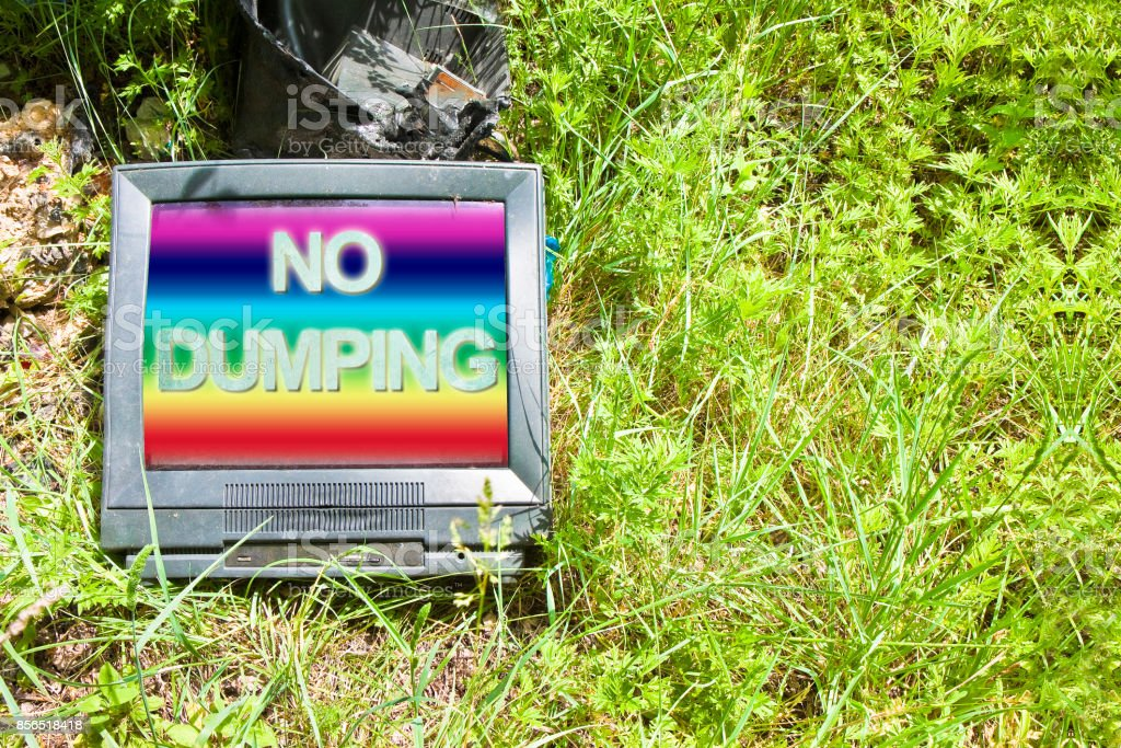 Old television CRT (Cathode ray tube) abandoned in nature with 'No Dumping' text - concept image with copy space stock photo