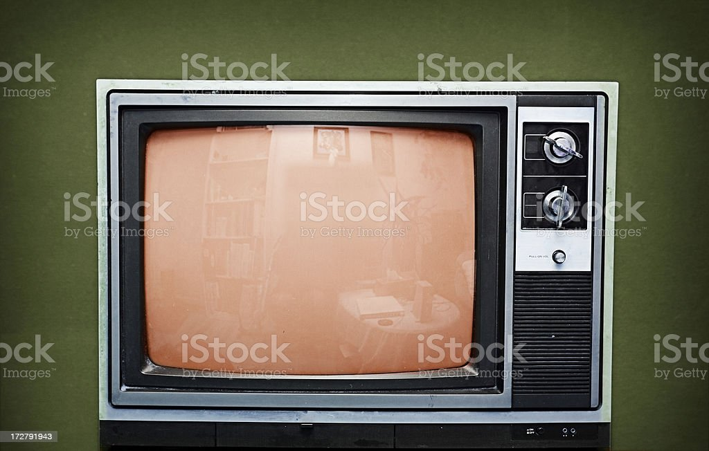 Old television set on a green background stock photo