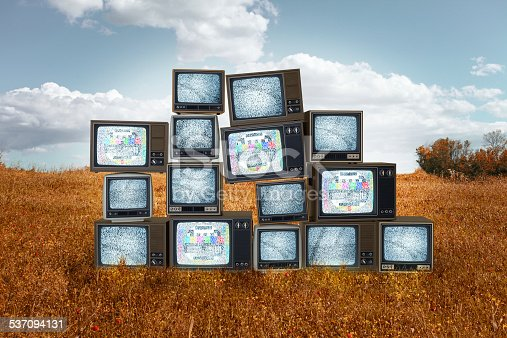 istock Old televisions stacked in the middle of grass field 537094131