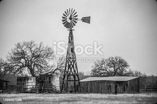 istock Old Texas wood windmill 2 cisterns barn trees pasture 1269567098