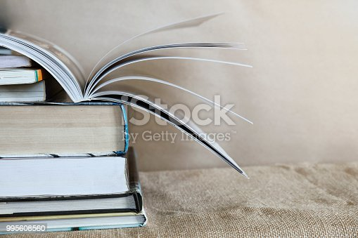 istock Old textbook stack on the sackcloth with the book turning pages on top 995608560