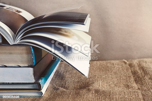 istock Old textbook stack on the sackcloth with the book turning pages on top 995608898