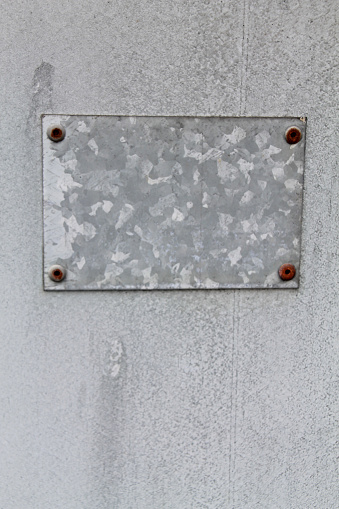 Old, texturized, galvanized metal background with screwed on metal patch with rusty screws