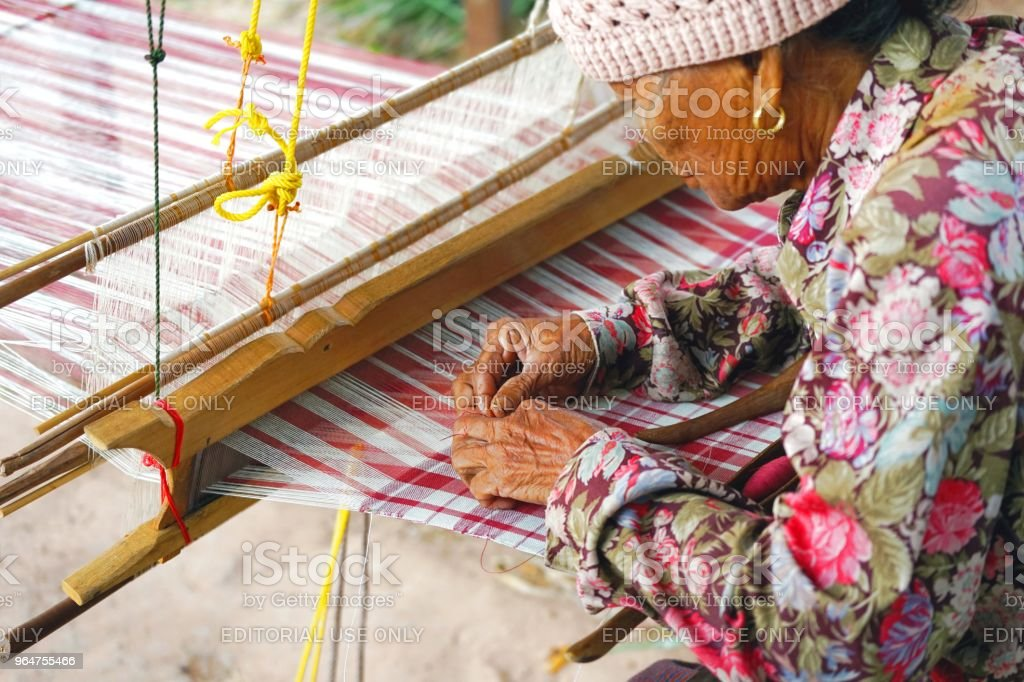 Old Thai woman using traditional household weaving machine or hand weaving loom for weaving the cloth. royalty-free stock photo