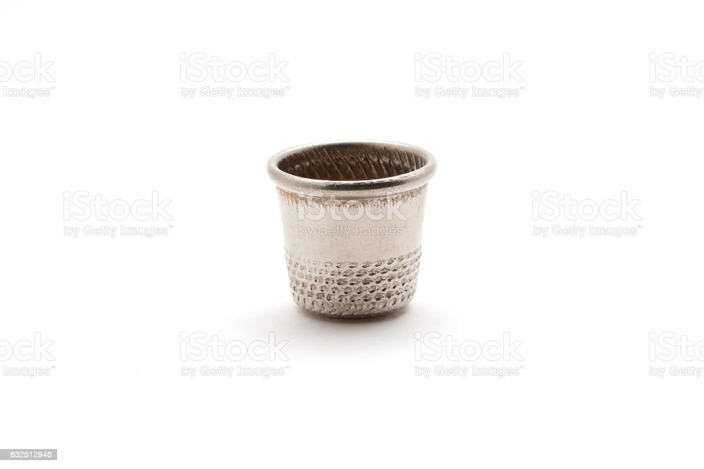 Old thimble for finger on a white background stock photo