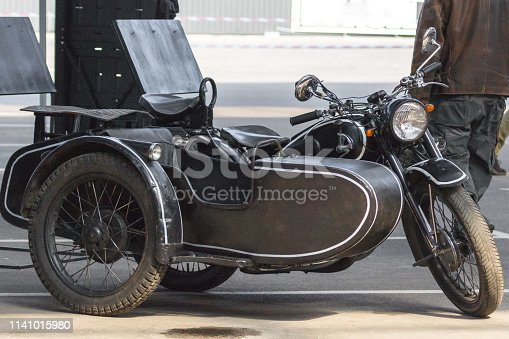 Three-wheeled motorcycle with a sidecar. Old Soviet motorcycle. Rare vehicle. Vintage motorcycle Izh. Passenger seat on the bike.