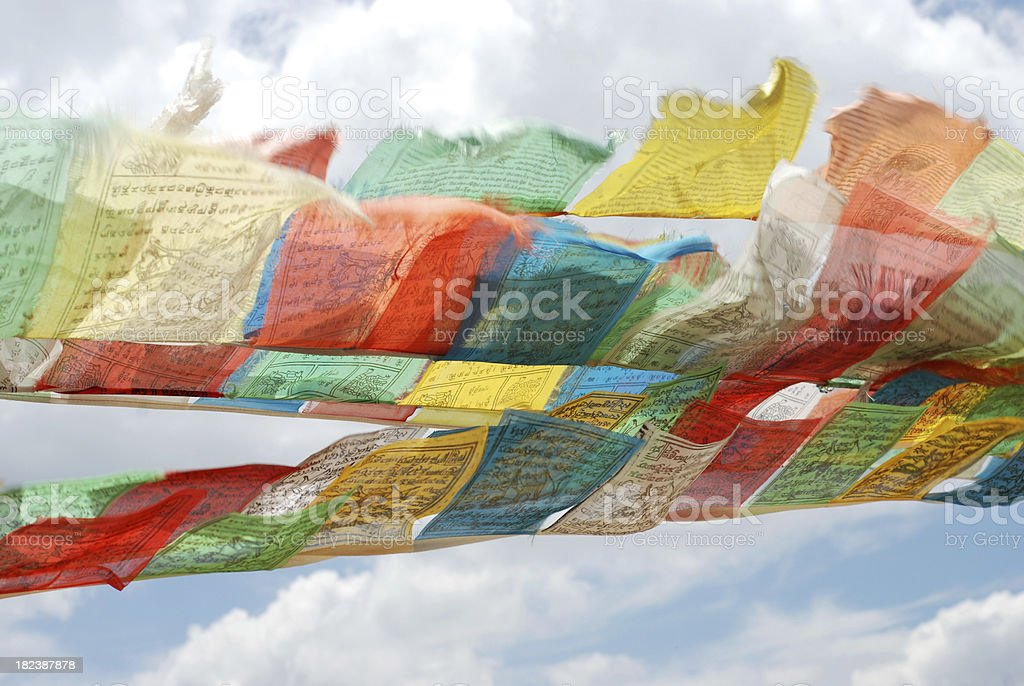 Old Tibetan Prayer Flags flying against a cloudy sky stock photo