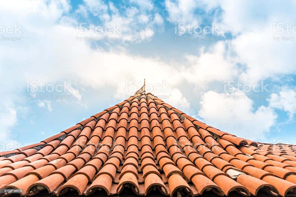 Old tiled roof with sky in background. stock photo