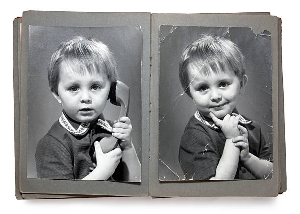 Old times style photobook of a child posing with a telephone Old album with the children's shabby photos (isolated) fine art portrait stock pictures, royalty-free photos & images