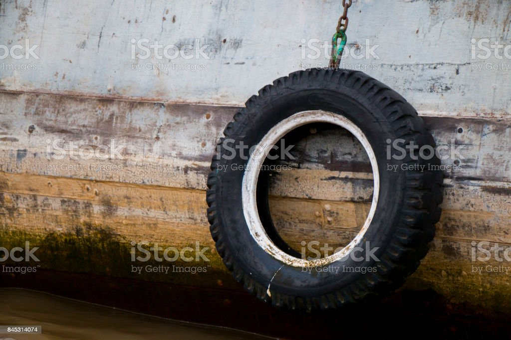 Old tire hanging from wooden boat side. stock photo