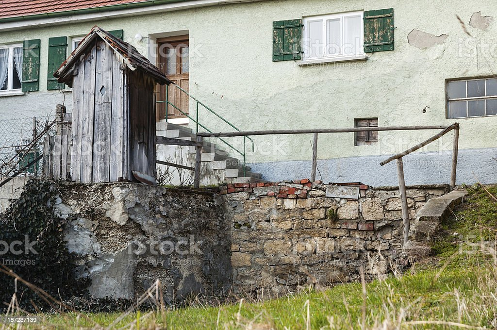 Old toilet cottage front of an house in a village royalty-free stock photo