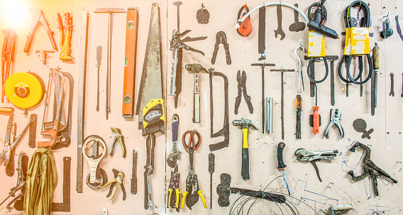 Old tools hanging on the wall in workshop.
