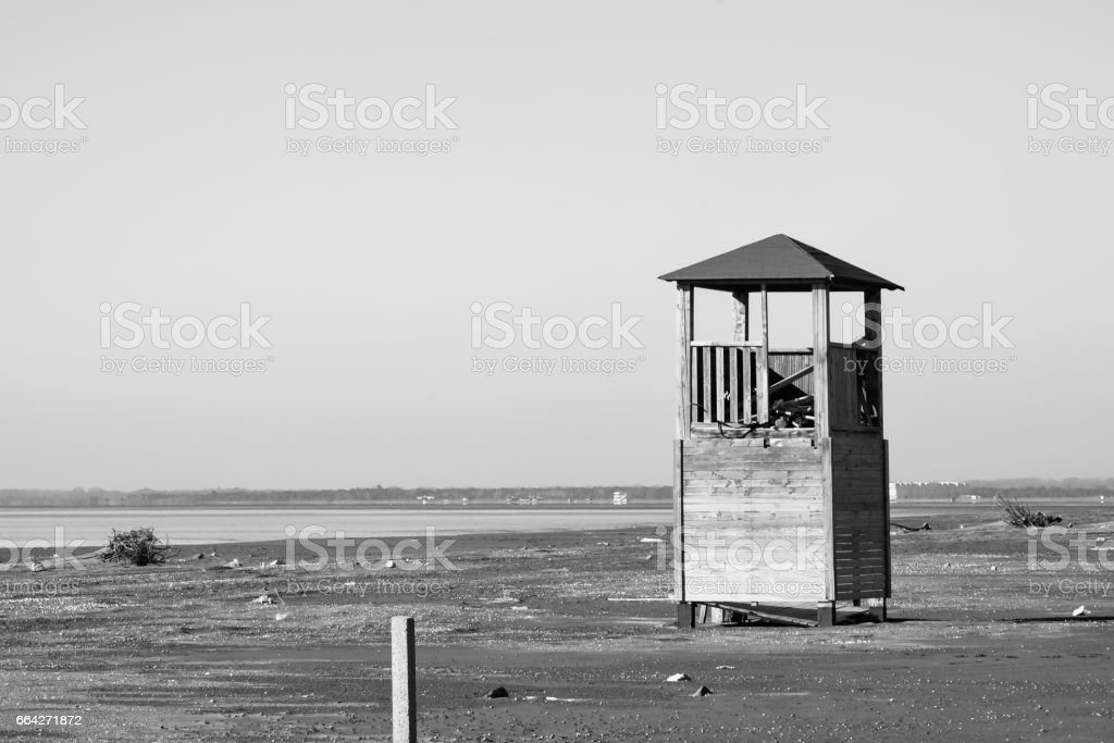 Old tower for lifeguards on the deserted beach in black and white royalty free stock