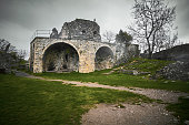 Old tower ruins of Anakopia fortress, New Athos, Abkhazia. Gray cloudy sky and green grass