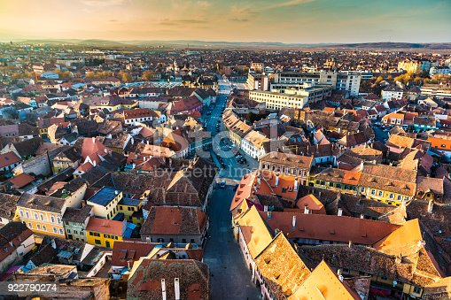 Color image depicting the ancient, medieval skyline of Sibiu, a city in the Transylvania region of Romania. In the foreground we can see two orthodox church spires, while beyond we can see traditional Germanic architecture of the town's buildings and houses spread out. Room for copy space.